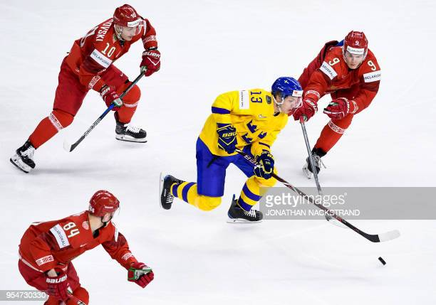 Sweden's Mattias Janmark vies for the puck with Belarus' players during the 2018 IIHF Men's Ice Hockey World Championship match between Sweden and...