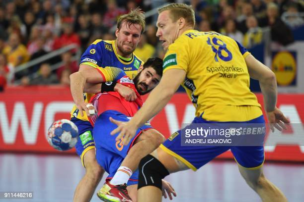 Sweden's Max Darj and Sweden's Frederic Pettersson hold off Spain's Eduardo Gurbindo during the final match of the Men's 2018 EHF European Handball...