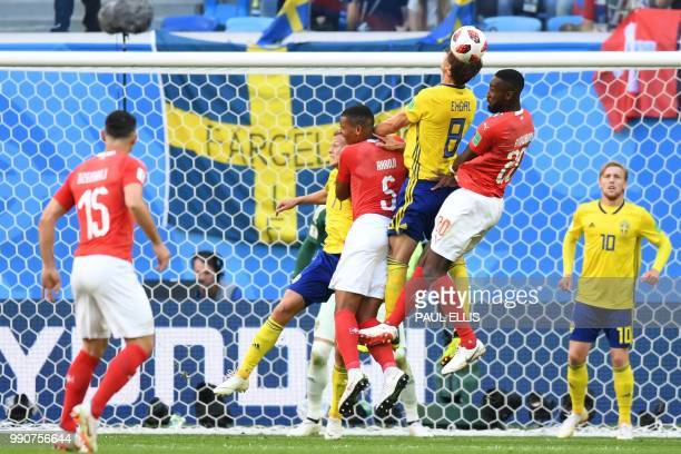 Sweden's midfielder Albin Ekdal heads the ball with Switzerland's defender Manuel Akanji and Switzerland's defender Johan Djourou during the Russia...