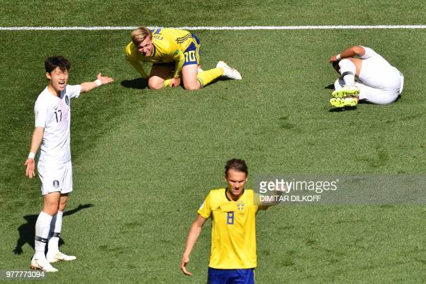 Sweden's midfielder Emil Forsberg and South Korea's forward Hwang Heechan react in pain following a collision during the Russia 2018 World Cup Group...