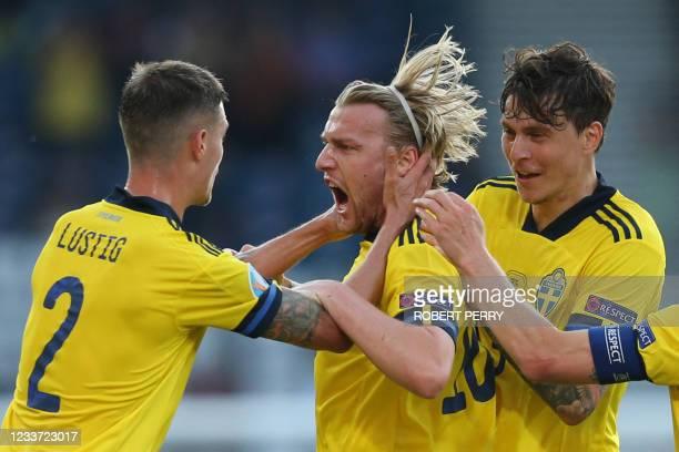 Sweden's midfielder Emil Forsberg celebrates with Sweden's defender Mikael Lustig and Sweden's defender Victor Lindelof R after scoring his team's...