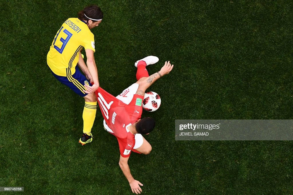 TOPSHOT - Sweden's midfielder Gustav Svensson (L) fights for the ball with Switzerland's midfielder Granit Xhaka (R) during the Russia 2018 World Cup round of 16 football match between Sweden and Switzerland at the Saint Petersburg Stadium in Saint Petersburg on July 3, 2018. (Photo by Jewel SAMAD / AFP) / RESTRICTED