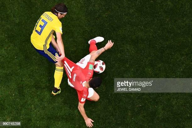 TOPSHOT Sweden's midfielder Gustav Svensson fights for the ball with Switzerland's midfielder Granit Xhaka during the Russia 2018 World Cup round of...