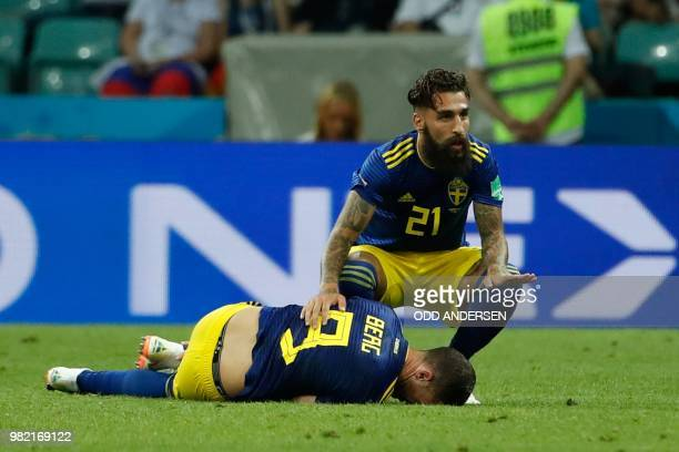 Sweden's midfielder Jimmy Durmaz helps his teammate Sweden's forward Marcus Berg laying on the football pitch after being injured during the Russia...
