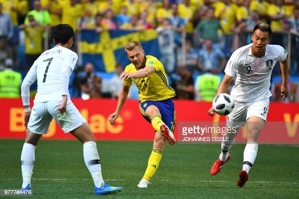 Sweden's midfielder Sebastian Larsson attempts a shot as he is marked by South Korea's forward Kim Shinwook during the Russia 2018 World Cup Group F...