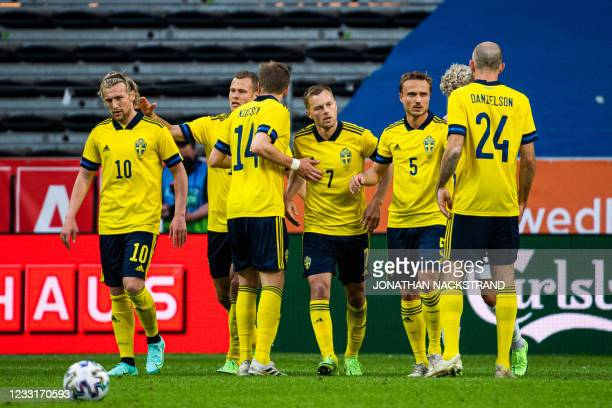Sweden's midfielder Sebastian Larsson celebrates with his teammates after scoring during the international friendly football match between Sweden and...