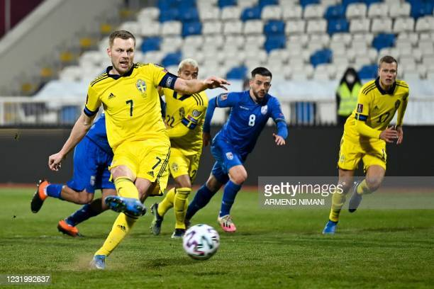 Sweden's midfielder Sebastian Larsson scores on a penalty kick during the FIFA World Cup Qatar 2022 qualification Group B football match between...