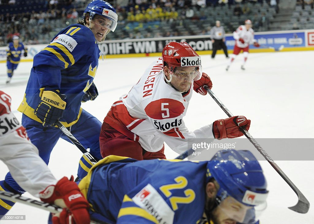 Sweden's Niklas Persson (R) and Sweden's Carl Gunnarsson (L) vies with Denmark's Daniel Nielsen (C) during the IIHF Ice Hockey World Championship quarter-final match Sweden vs Denmark in the southern German city of Mannheim on May 20, 2010. The 2010 IIHF Ice Hockey World Championships are taking place in Germany from May 7 to 23, 2010.