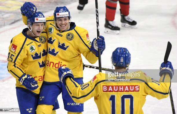 Sweden's Oscar Moeller and Paer Lindholm and Joakim Lindstroem celebrate Lindholm's 0-2 third period goal during the match between Canada and Sweden...