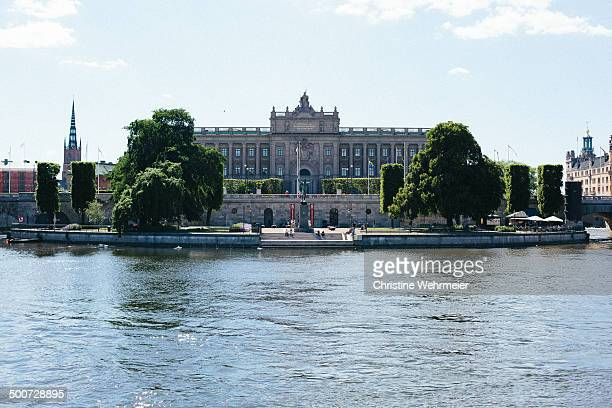 Sweden's parliament house sits on an island called Helgeandsholmen and is surrounded by water. Photo taken on a sunny day in summer