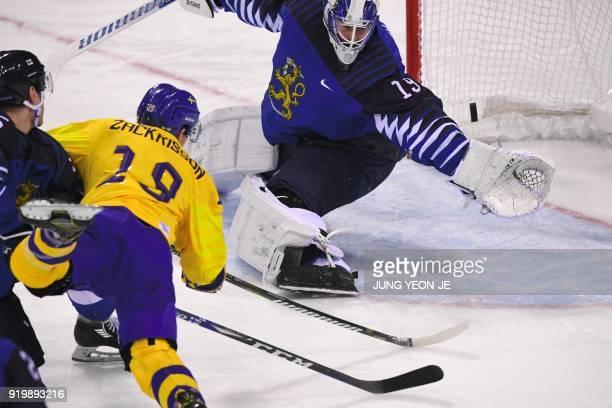 Sweden's Patrik Zackrisson scores against Finland's Mikko Koskinen in the men's preliminary round ice hockey match between Sweden and Finland during...