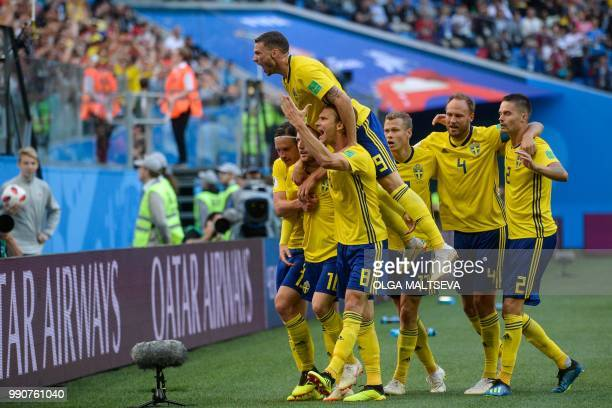 TOPSHOT Sweden's players celebrate after midfielder Emil Forsberg scored during the Russia 2018 World Cup round of 16 football match between Sweden...