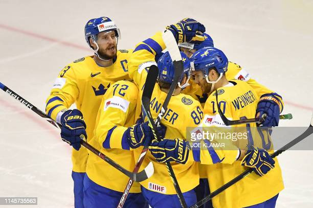 Sweden's players celebrate scoring during the IIHF Men's Ice Hockey World Championships quarter-final match between Finland and Sweden on May 23,...