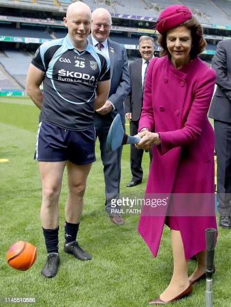 Sweden's Queen Silvia tries her hand at hurling, at Croke Park, the home of the Gaelic Athletic Association , in Dublin on May 22 on the first day of...
