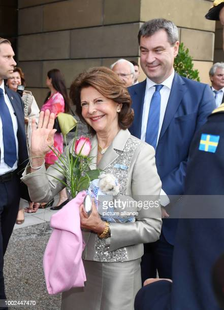 Sweden's Queen Silvia waves accompanied by Bavarian Finance Minister Markus Soeder at the Residenz in Munich Germany 24 July 2017 The Swedish royal...