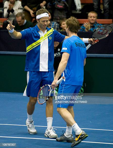 Sweden's Robert Lindstedt jubilates with Simon Aspelin after wining their Davis Cup first round doubles match against Russia's Igor Kunitsyn and...