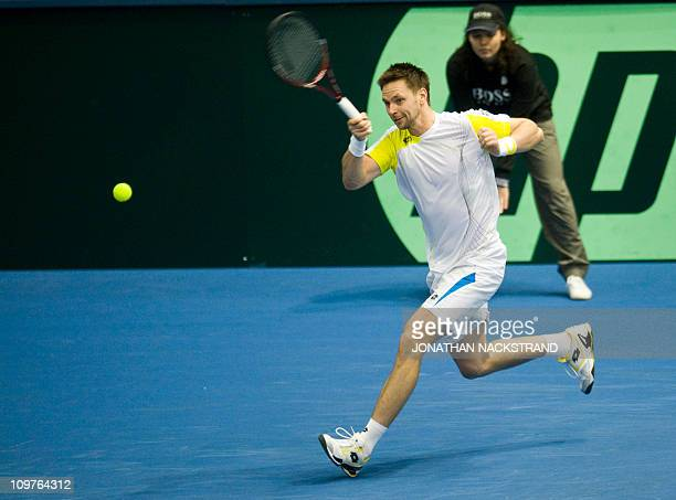 """Sweden's Robin Soderling returns a ball against Russia's Igor Andreev during their Davis Cup first round singles match in """"Borashallen"""" in Boras,..."""
