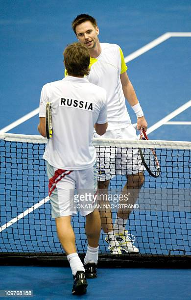 Sweden's Robin Soderling shakes hand with Russia's Igor Andreev after their Davis Cup first round singles match in Borashallen in Boras east of...