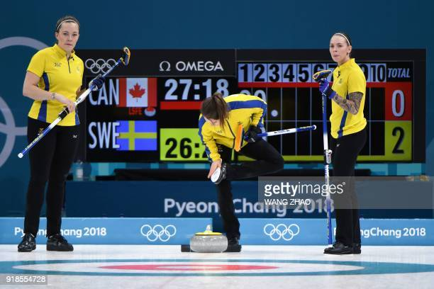 Sweden's Sara McManus cleans her shoes during the curling women's round robin session between Canada and Sweden during the Pyeongchang 2018 Winter...
