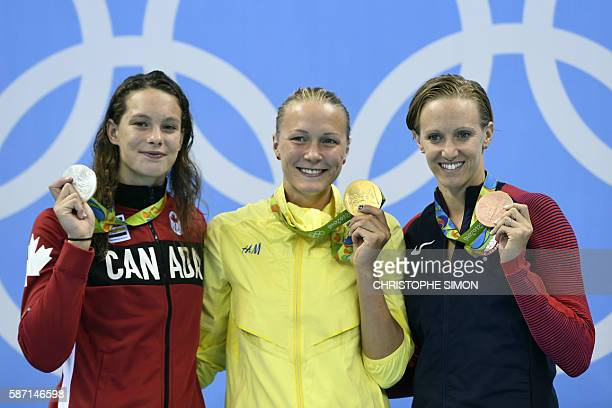 Sweden's Sarah Sjostrom poses on the podium with silver medallist Canada's Penny Oleksiak and bronze medallist USA's Dana Vollmer after she won the...