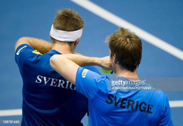Sweden's Simon Aspelin talks with Robert Lindstedt during their Davis Cup first round doubles match against Russia's Igor Kunitsyn and Dmitry...