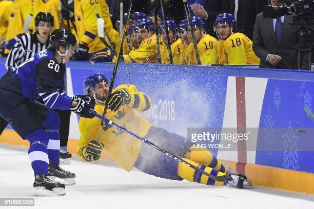 Sweden's Simon Bertilsson falls to the ice against Finland's Eeli Tolvanen as they fight for the puck in the men's preliminary round ice hockey match...