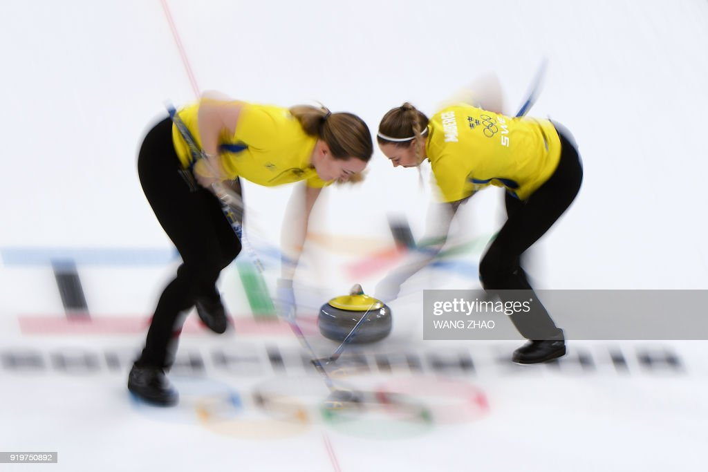 Sweden's Sofia Mabergs (R) brushes in front of the stone during the curling women's round robin session between Britain and Sweden during the Pyeongchang 2018 Winter Olympic Games at the Gangneung Curling Centre in Gangneung on February 18, 2018. / AFP PHOTO / WANG Zhao