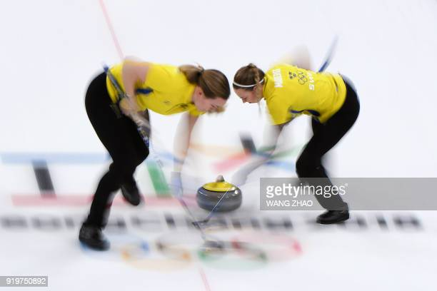 Sweden's Sofia Mabergs brushes in front of the stone during the curling women's round robin session between Britain and Sweden during the Pyeongchang...