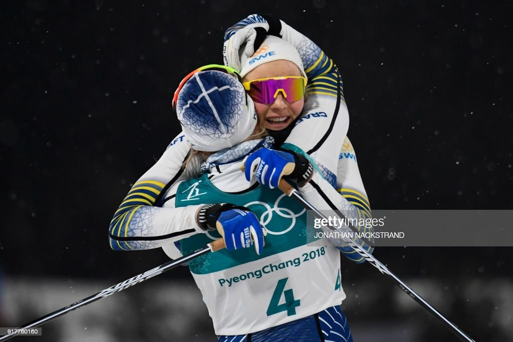 TOPSHOT - Sweden's Stina Nilsson is congratulated by Sweden's Hanna Falk (4) after winning gold in the women's cross-country individual sprint classic final at the Alpensia cross country ski centre during the Pyeongchang 2018 Winter Olympic Games on February 13, 2018 in Pyeongchang. / AFP PHOTO / Jonathan NACKSTRAND