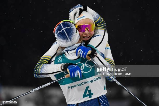 TOPSHOT Sweden's Stina Nilsson is congratulated by Sweden's Hanna Falk after winning gold in the women's crosscountry individual sprint classic final...