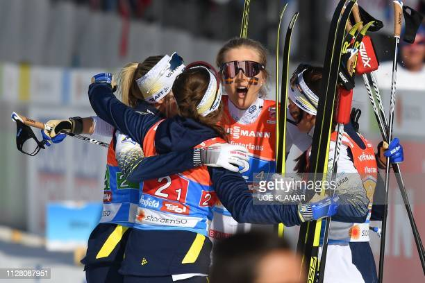 Sweden's Stina Nilsson is congratulated by teammates Sweden's Ebba Andersson Sweden's Frida Karlsson Sweden's Charlotte Kalla after she crossed the...