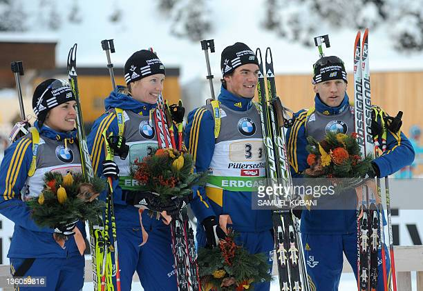 Sweden's team Elisabeth Hogberg Anna Maria Nilsson Fredrik Lindstrom and Carl Johan Bergman pose in the finish area of the mixed 2x6 2x75 km relay of...