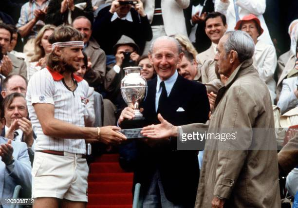Sweden's tennis player Bjorn Borg receives the Winner's Trophy from former tennis musketeers Jean Borotra and Henri Cochet here 09 june 1979 after...