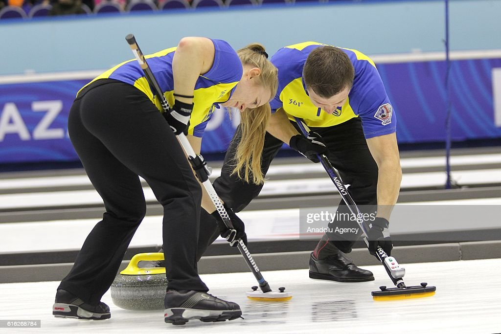 Sweden's third Jennie Waahlin (L) and second Joakim Flyg (R) in action during semi-finals the game between Sweden and Scotland within the World Mixed Curling Championship 2016 at the Sport Palace in Kazan, Russia on October 22, 2016.