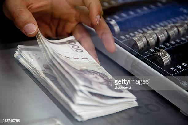Swedish 1000 kronor notes are handled by a cashier in this arranged photograph inside a currency exchange in Malmo, Sweden, on Tuesday, May 14, 2013....