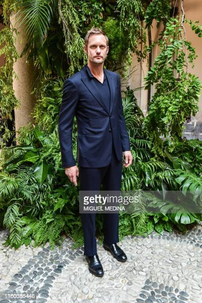 Swedish actor Alexander Skarsgard poses as he arrives to attend the presentation of fashion house Armani's women's and men's spring/summer 2020...
