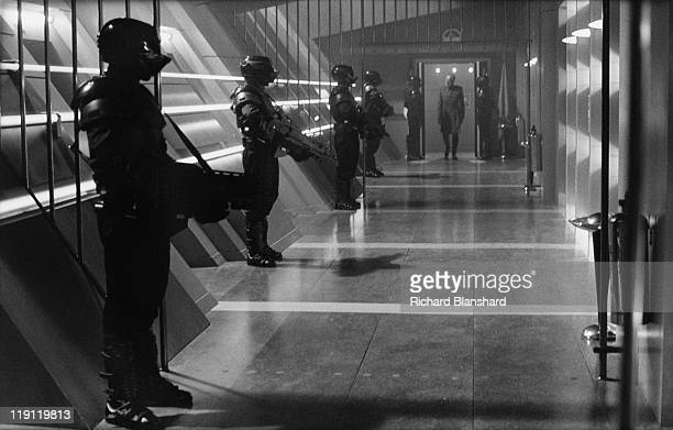 Swedish actor Max von Sydow enters a corridor lined with armed guards in a scene from the dystopian scifi film 'Judge Dredd' 1995