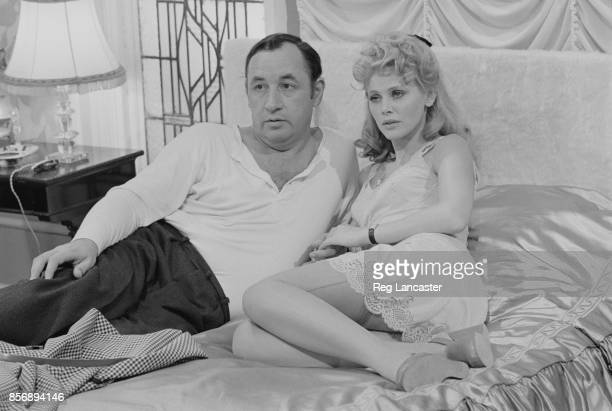 Swedish actress and singer Britt Ekland and French actor Philippe Noiret sit on a bed together on the set of British comedydrama film 'A Time for...