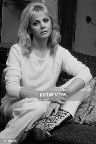 Swedish actress and singer Britt Ekland wearing white jumper and trousers and snakeskin boots UK 24th December 1984