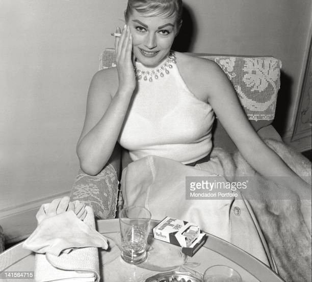 Swedish actress Anita Ekberg smoking a Marlboro cigarette sitting in an armchair at Hotel Excelsior Florence May 1956