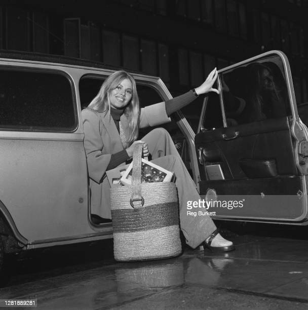 Swedish actress Britt Ekland getting out of a car in London with a basket full of Christmas decorations, UK, 2nd December 1972.