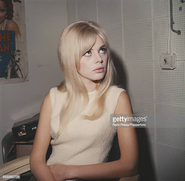 Swedish actress Britt Ekland pictured wearing a cream coloured sleeveless dress and sitting in a chair circa 1963