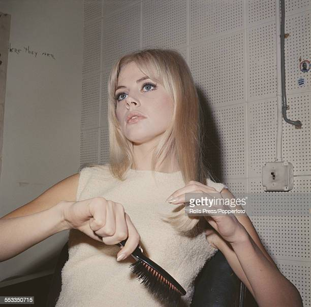 Swedish actress Britt Ekland pictured wearing a cream coloured sleeveless dress and combing her hair circa 1963