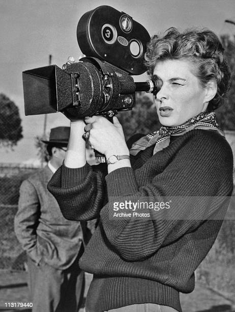 Swedish actress Ingrid Bergman using a film camera on set of the movie 'We, the Women' in 1953.