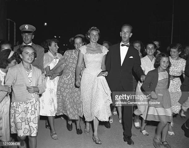 Swedish actress Ingrid Bergman, wearing a lace dress, portrayed while walking in the street followed by a crowd of women and girls, Venice, 1950.