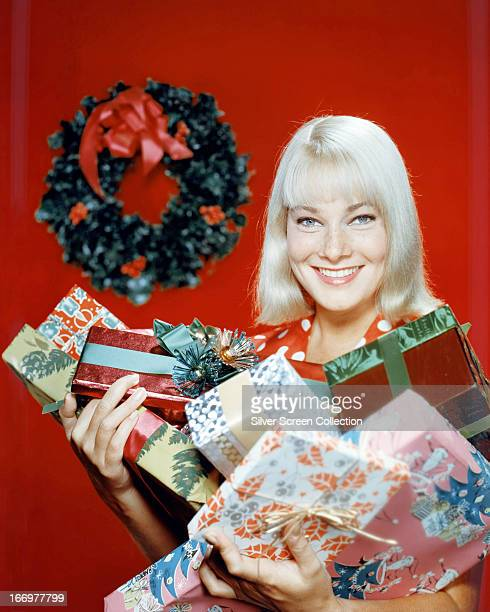 Swedish actress May Britt holding a selection of giftwrapped Christmas presents circa 1960