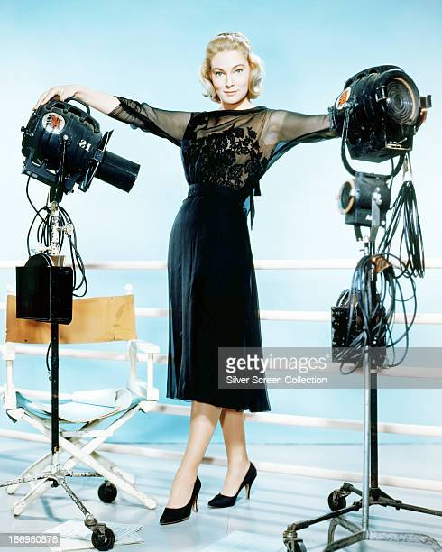 Swedish actress May Britt posing in a black outfit next to studio lights circa 1955