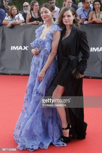 Swedish actress Rebecca Ferguson and US actress Michelle Monaghan pose on the red carpet as they arrive to attend the world premiere of his new film...