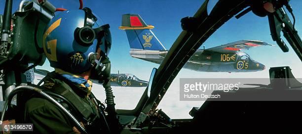 A Swedish Air Force pilot flies alongside another Saab 105 training jet