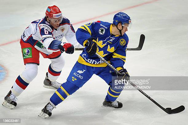 Swedish Andreas Falk fights for the puck with Russian Denis Denisov during Channel One Cup hockey match the event of the Euro Hockey Tour in Moscow...